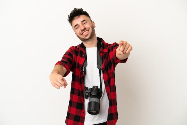 Kaukasischer mann des jungen fotografen lokalisiert auf weißem hintergrund zeigt mit dem finger auf sie, während er lächelt