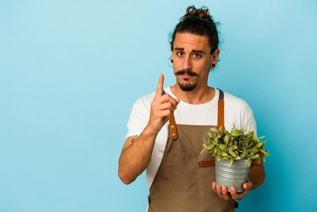 Kaukasischer mann des jungen gärtners, der eine anlage lokalisiert auf blauem hintergrund hält, der nummer eins mit dem finger zeigt.