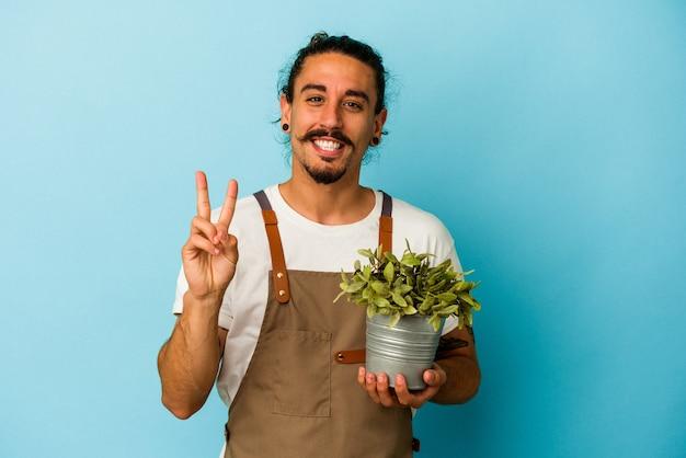 Kaukasischer mann des jungen gärtners, der eine anlage lokalisiert auf blauem hintergrund hält, der nummer zwei mit den fingern zeigt.