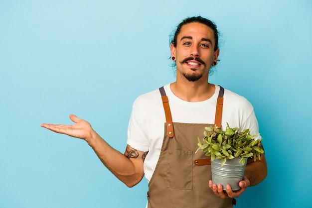Kaukasischer mann des jungen gärtners, der eine pflanze lokalisiert auf blauem hintergrund hält, der einen kopienraum auf einer palme zeigt und eine andere hand auf taille hält.