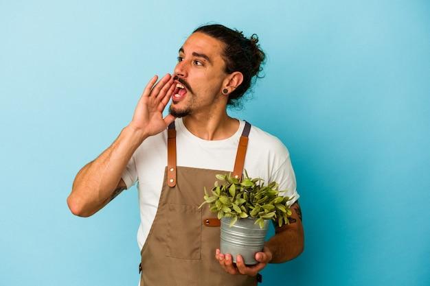 Kaukasischer mann des jungen gärtners, der eine pflanze lokalisiert auf blauem hintergrund hält, schreit und palme nahe geöffnetem mund hält