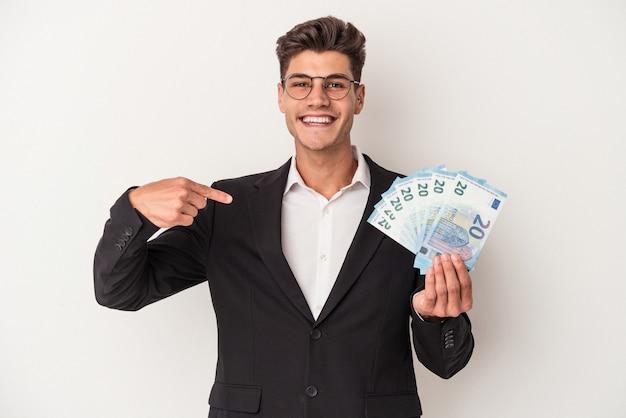 Kaukasischer mann des jungen geschäfts, der banknoten einzeln auf weißem hintergrund hält, der mit der hand auf einen hemdkopienraum zeigt, stolz und selbstbewusst