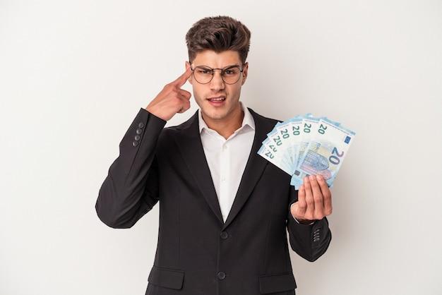 Kaukasischer mann des jungen geschäfts, der banknoten lokalisiert auf weißem hintergrund hält, der eine enttäuschungsgeste mit dem zeigefinger zeigt.
