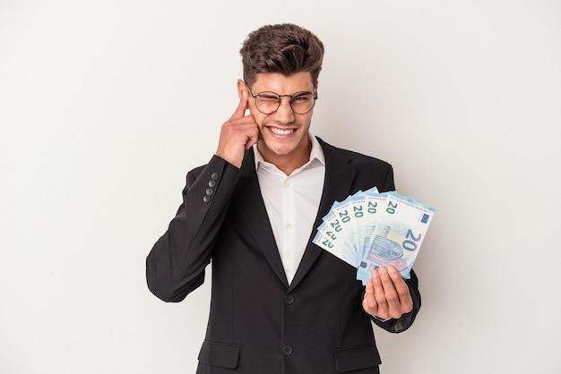 Kaukasischer mann des jungen geschäfts, der banknoten lokalisiert auf weißem hintergrund hält, der ohren mit den händen bedeckt.