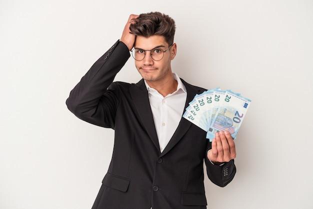 Kaukasischer mann des jungen geschäfts, der banknoten lokalisiert auf weißem hintergrund hält, der schockiert ist, hat sie sich an wichtiges treffen erinnert.