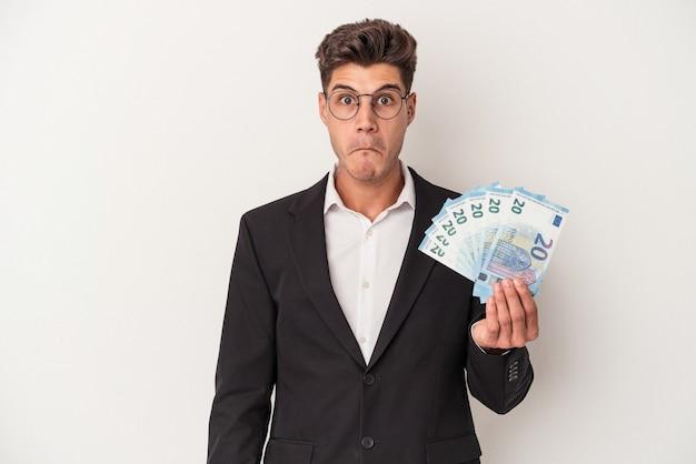 Kaukasischer mann des jungen geschäfts, der banknoten lokalisiert auf weißem hintergrund hält, zuckt die schultern und offene augen verwirrt.