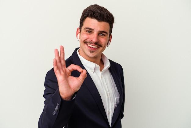 Kaukasischer mann des jungen geschäfts, der drahtlose kopfhörer lokalisiert auf weißem hintergrund trägt, fröhlich und selbstbewusst, die ok geste zeigen.