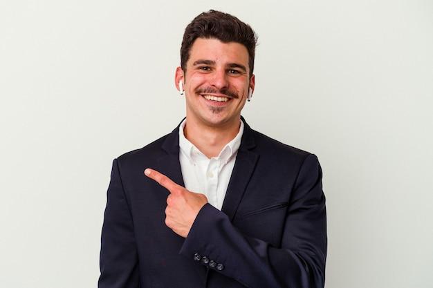 Kaukasischer mann des jungen geschäfts, der drahtlose kopfhörer lokalisiert auf weißem hintergrund trägt, lächelt und zeigt beiseite und zeigt etwas an der leerstelle.