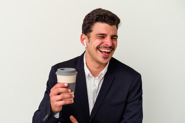Kaukasischer mann des jungen geschäfts, der drahtlose kopfhörer trägt und kaffee hält, der auf weißem hintergrund lokalisiert wird, lacht und spaß hat.