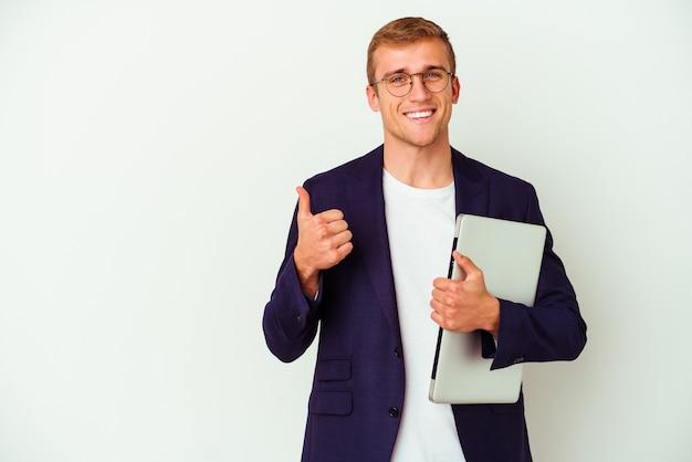 Kaukasischer mann des jungen geschäfts, der einen laptop lokalisiert auf weißem hintergrund hält, lächelt und daumen hoch