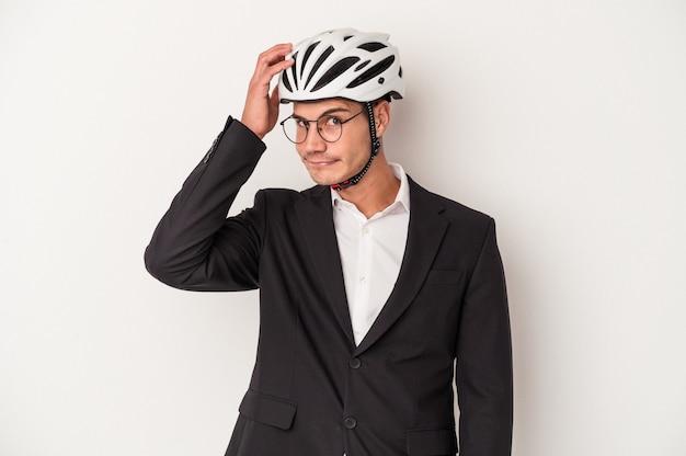 Kaukasischer mann des jungen geschäfts, der fahrradhelm lokalisiert auf weißem hintergrund hält, der schockiert ist, hat sie sich an wichtiges treffen erinnert.