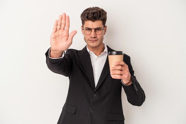 Kaukasischer mann des jungen geschäfts, der kaffee zum mitnehmen lokalisiert auf weißem hintergrund hält, der mit ausgestreckter hand steht, die stoppschild zeigt und sie verhindert.