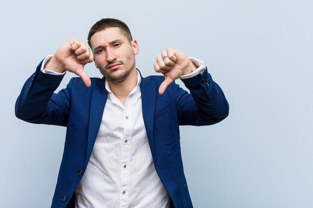 Kaukasischer mann des jungen geschäfts, der unten daumen zeigt und abneigung ausdrückt