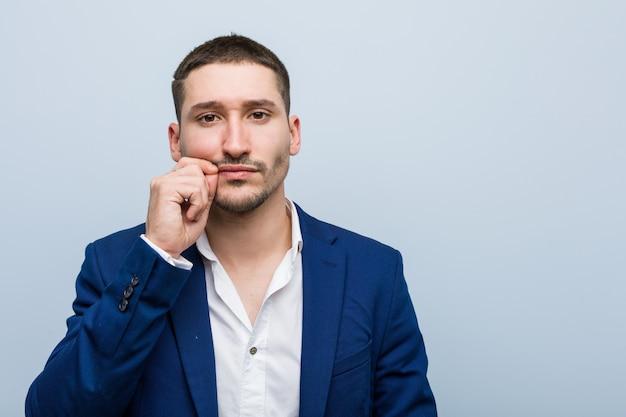 Kaukasischer mann des jungen geschäfts mit den fingern auf den lippen, die ein geheimnis halten.