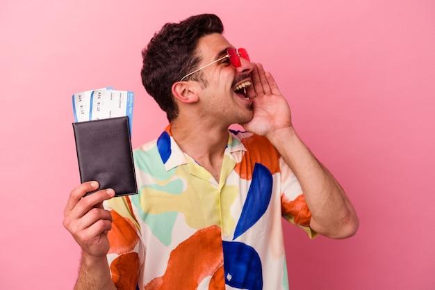 Kaukasischer mann des jungen reisenden, der einen reisepass einzeln auf rosafarbenem hintergrund hält, der schreit und palme nahe geöffnetem mund hält.