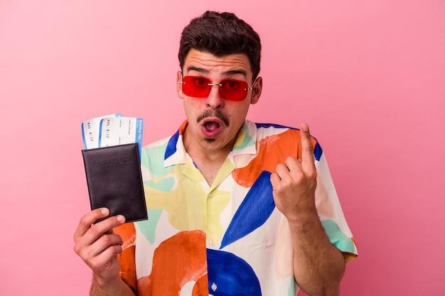 Kaukasischer mann des jungen reisenden, der einen reisepass einzeln auf rosafarbenem hintergrund hält und eine großartige idee hat, konzept der kreativität.