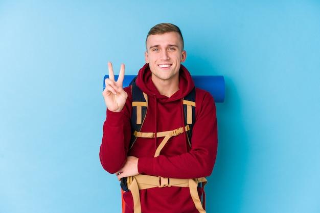 Kaukasischer mann des jungen reisenden, der nummer zwei mit den fingern zeigt.