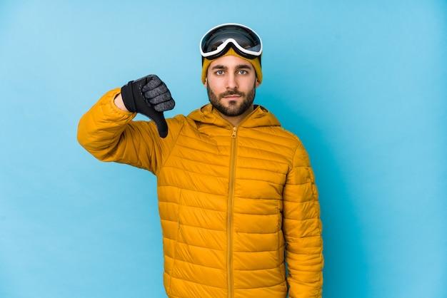 Kaukasischer mann des jungen skifahrers lokalisiert, eine abneigungsgeste, daumen unten zeigend. uneinigkeit konzept.