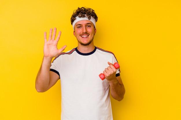 Kaukasischer mann des jungen sports, der eine hantel lokalisiert auf einem gelben hintergrund hält, der fröhlich lächelt und nummer fünf mit den fingern zeigt