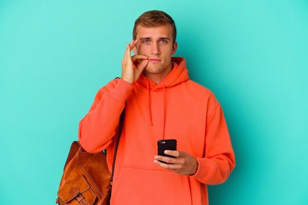 Kaukasischer mann des jungen studenten, der ein handy lokalisiert auf blauem hintergrund mit den fingern auf den lippen hält, die ein geheimnis halten.