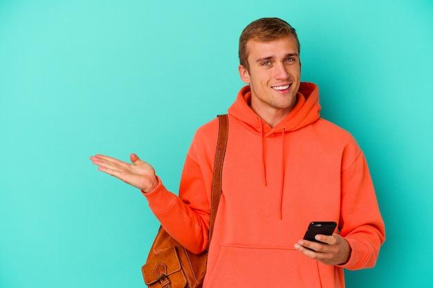 Kaukasischer mann des jungen studenten, der ein mobiltelefon lokalisiert auf blau hält, das einen kopienraum auf einer handfläche zeigt und eine andere hand auf taille hält.