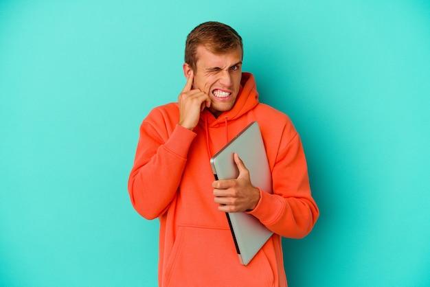 Kaukasischer mann des jungen studenten, der einen laptop lokalisiert auf blau bedeckenden ohren mit den händen hält.
