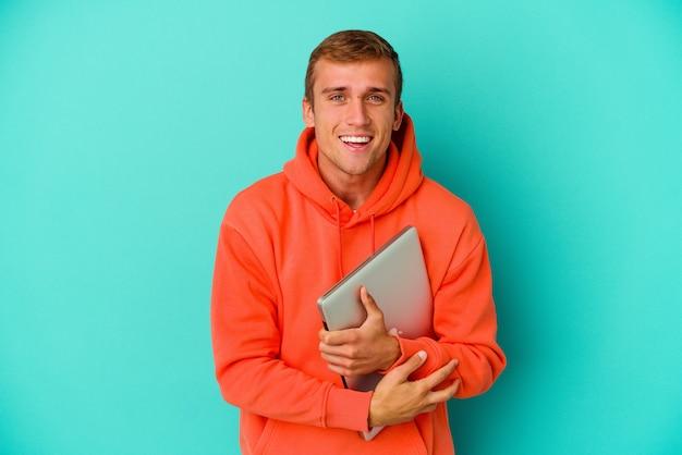 Kaukasischer mann des jungen studenten, der einen laptop lokalisiert auf blauem hintergrund hält, lacht und spaß hat