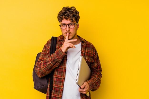 Kaukasischer mann des jungen studenten, der einen laptop lokalisiert auf gelbem hintergrund hält, der ein geheimnis hält oder um stille bittet.