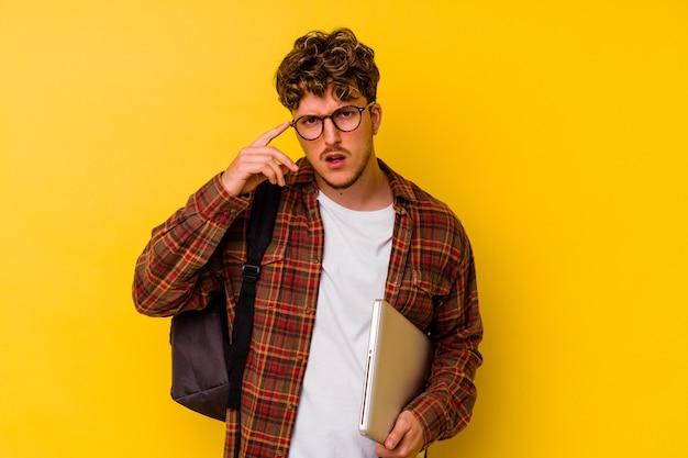 Kaukasischer mann des jungen studenten, der einen laptop lokalisiert auf gelbem hintergrund hält, der eine enttäuschungsgeste mit dem zeigefinger zeigt.