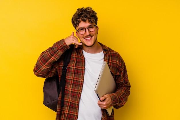 Kaukasischer mann des jungen studenten, der einen laptop lokalisiert auf gelbem hintergrund hält, der eine handyanrufgeste mit den fingern zeigt.