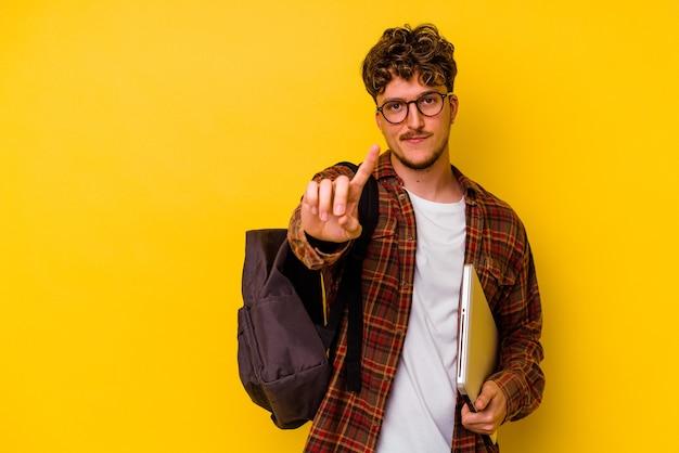 Kaukasischer mann des jungen studenten, der einen laptop lokalisiert auf gelbem hintergrund hält, der nummer eins mit finger zeigt.