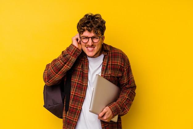Kaukasischer mann des jungen studenten, der einen laptop lokalisiert auf gelbem hintergrund hält, der ohren mit händen bedeckt.