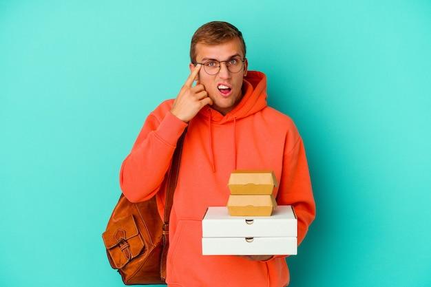 Kaukasischer mann des jungen studenten, der hamburger und pizzas lokalisiert auf blauem hintergrund hält, der eine enttäuschungsgeste mit dem zeigefinger zeigt.