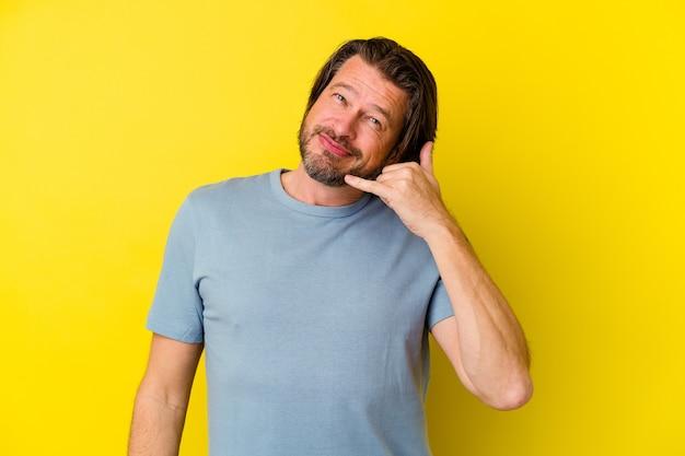 Kaukasischer mann des mittelalters lokalisiert auf gelbem hintergrund, der eine handy-anrufgeste mit den fingern zeigt.