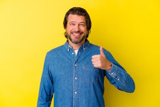 Kaukasischer mann des mittelalters lokalisiert auf gelbem hintergrund, der lächelt und daumen aufhebt