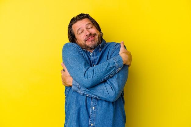 Kaukasischer mann des mittelalters lokalisiert auf gelben wandumarmungen, sorglos lächelnd und glücklich