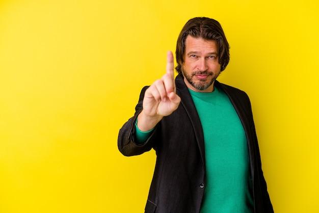 Kaukasischer mann des mittelalters lokalisiert auf gelber wand, die nummer eins mit finger zeigt