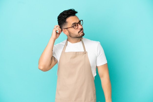 Kaukasischer mann des restaurantkellners lokalisiert auf blauem hintergrund, der zweifel hat und mit verwirrendem gesichtsausdruck