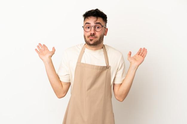 Kaukasischer mann des restaurantkellners lokalisiert auf weißem hintergrund, der zweifel hat, während er die hände hebt