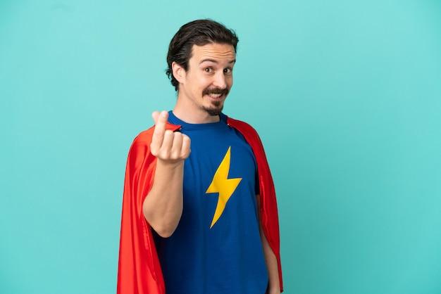Kaukasischer mann des superhelden lokalisiert auf blauem hintergrund, der geldgeste macht