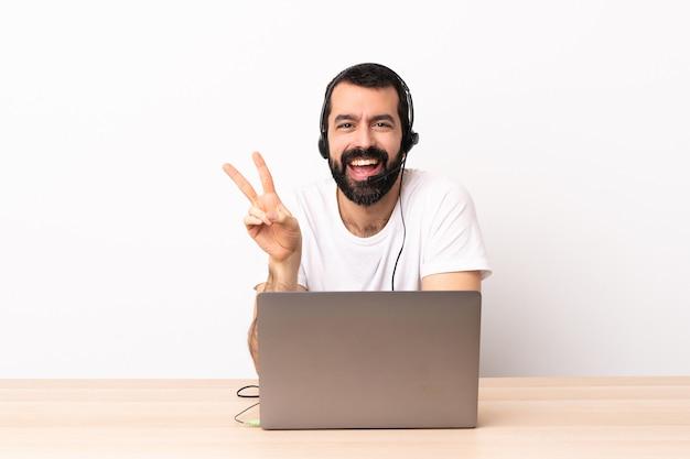 Kaukasischer mann des telemarketers, der mit einem headset und mit einem lächelnden laptop arbeitet und siegeszeichen zeigt.