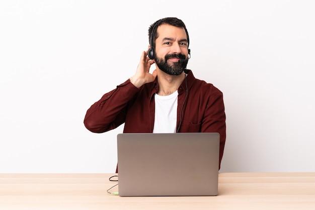 Kaukasischer mann des telemarketers, der mit einem headset und mit lachendem laptop arbeitet.