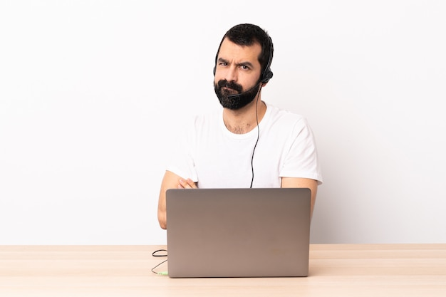Kaukasischer mann des telemarketers, der mit einem headset und mit laptop arbeitet, der sich verärgert fühlt.