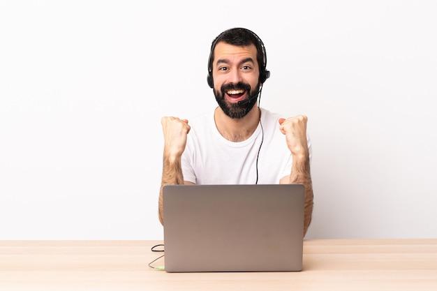 Kaukasischer mann des telemarketers, der mit einem headset und mit laptop arbeitet und einen sieg in der siegerposition feiert.