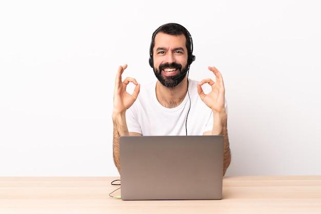 Kaukasischer mann des telemarketers, der mit einem kopfhörer arbeitet und mit laptop, der okayzeichen mit zwei händen zeigt.