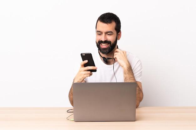 Kaukasischer mann des telemarketers, der mit einem kopfhörer arbeitet und mit laptop eine nachricht mit dem handy sendet.