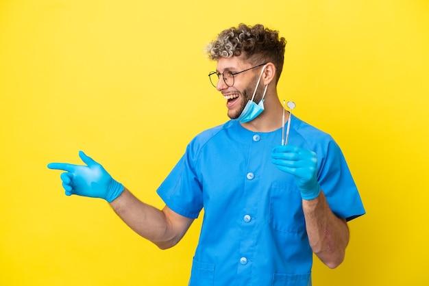 Kaukasischer mann des zahnarztes, der werkzeuge einzeln auf gelbem hintergrund hält, der mit dem finger zur seite zeigt und ein produkt präsentiert