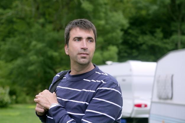 Kaukasischer mann entspannte sich auf kampierender wiese