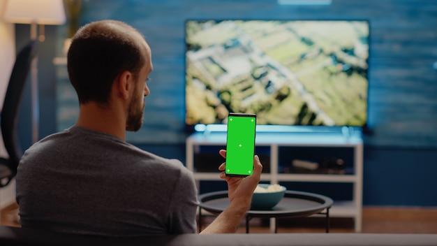Kaukasischer mann hält vertikal smartphone mit grünem bildschirm