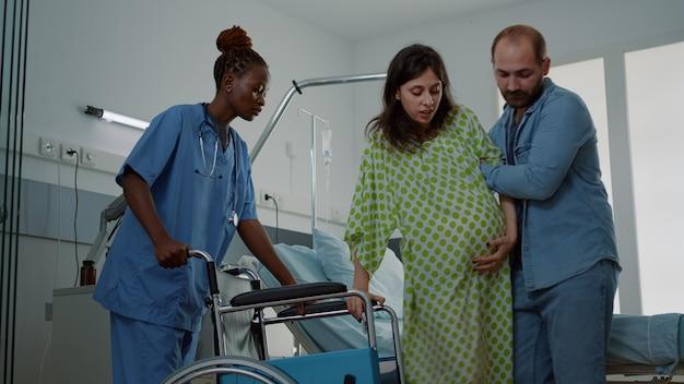 Kaukasischer mann hilft schwangerer frau in der krankenstation